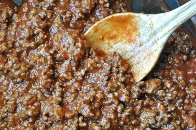 ground beef with sauce and wood spoon