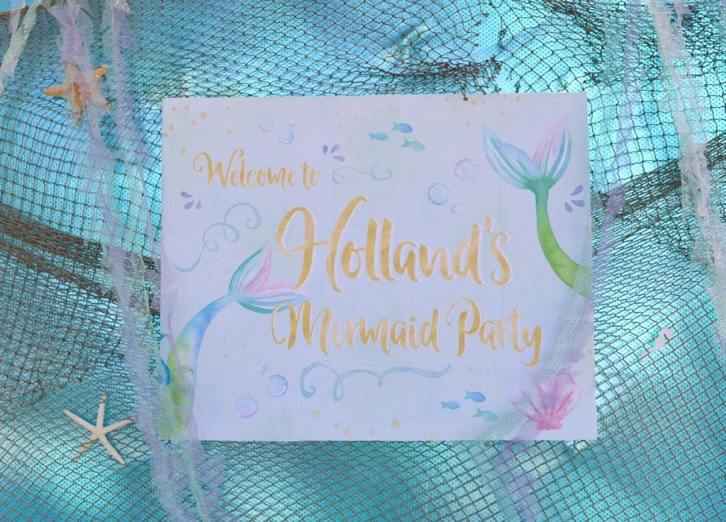 Mermaid party table backdrop made from a printable. Print on multiple pages and glue on foam board to make a large sign!