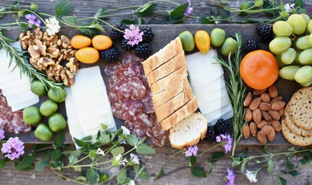 charcuterie board with meat, cheese, nuts, fruit