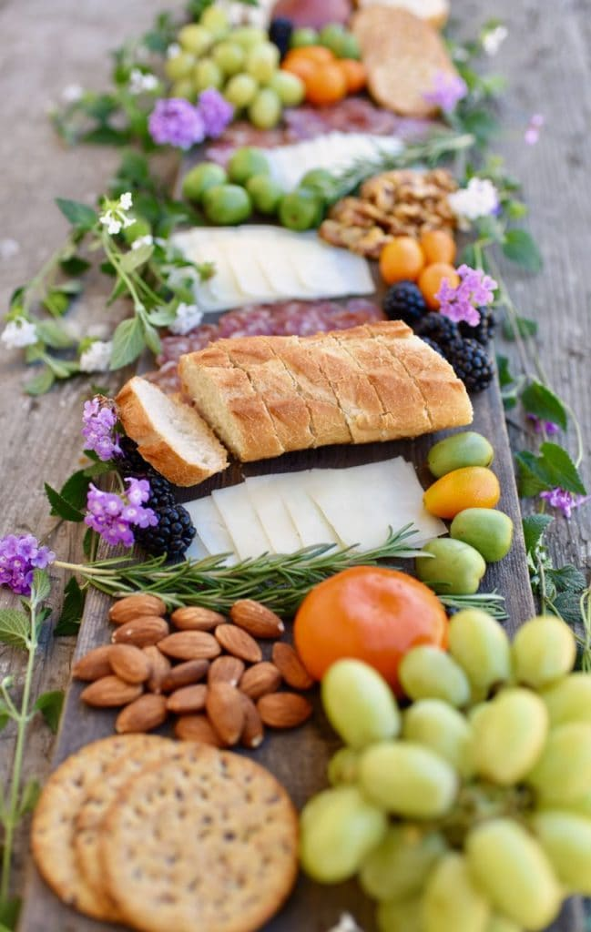 long wood platter with meat, cheese, bread, fruit