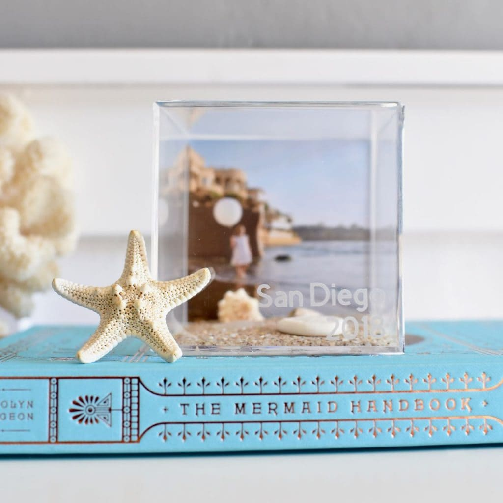 DIY vacation memory cube tutorial. Preserve those memories with a clear memory box! Just add photos and mementos from vacation to a clear acrylic box, then add the date and destination onto the front with etch vinyl!