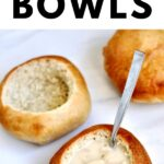 Homemade bread bowls filled with soup and a spoon