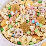 white bowl filled with leprechaun bait Lucky Charms cereal, popcorn, gold coins, and green candy