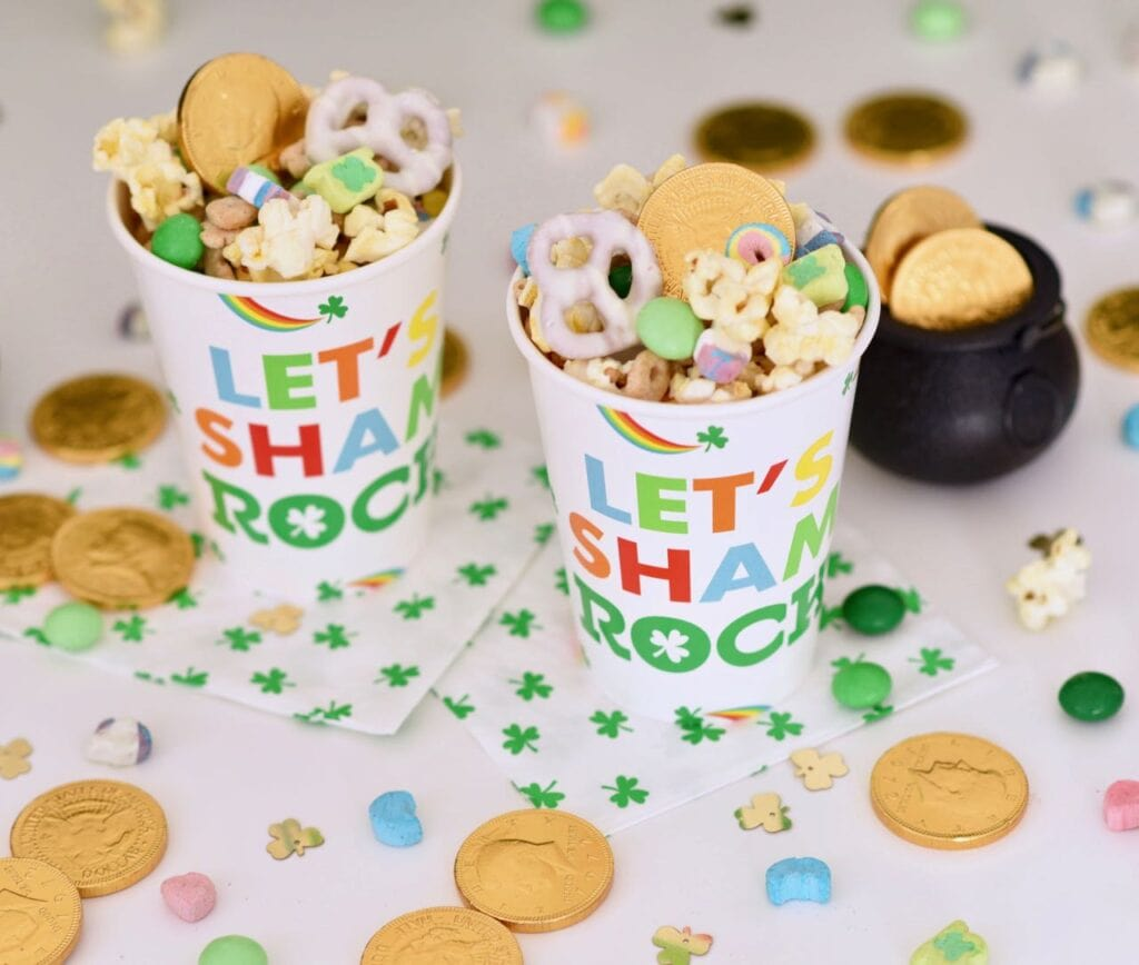two cups with gold coins, Lucky Charms cereal, and popcorn inside
