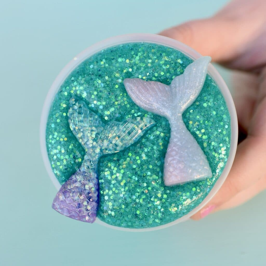 Glitter mermaid slime in plastic container with two mermaid tails