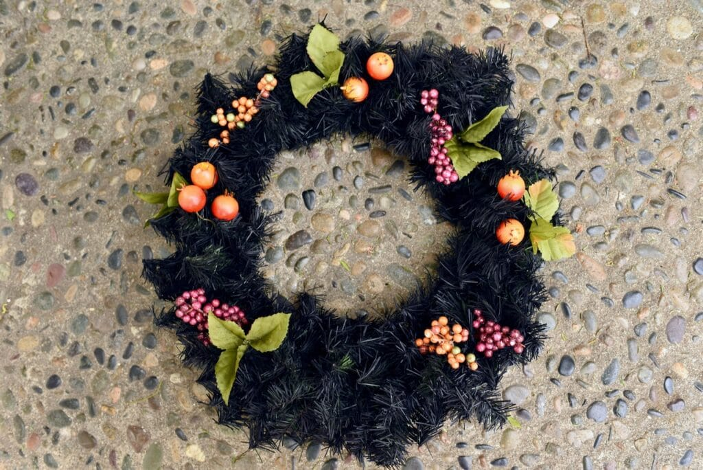 black wreath with orange and purple berries