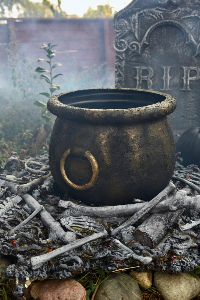Large witch cauldron on fake fire with bones