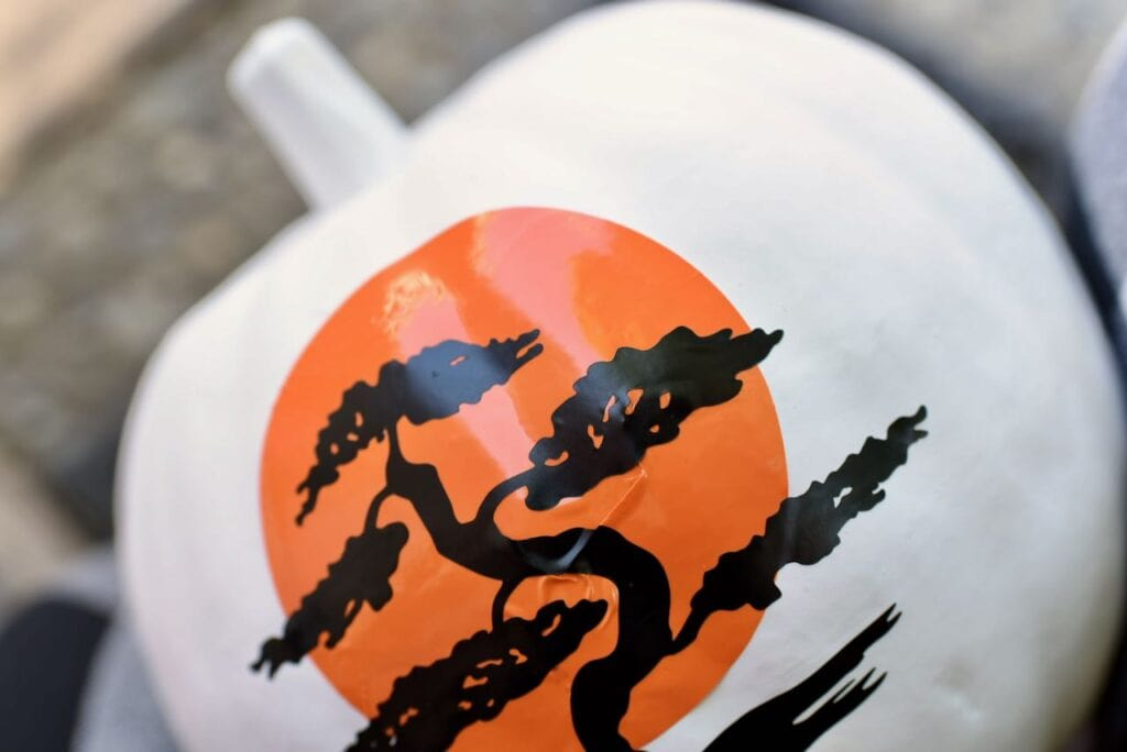 White pumpkin with orange sun and black tree