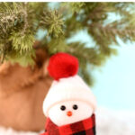DIY snowman ornament with scarf and hat in front of Christmas tree