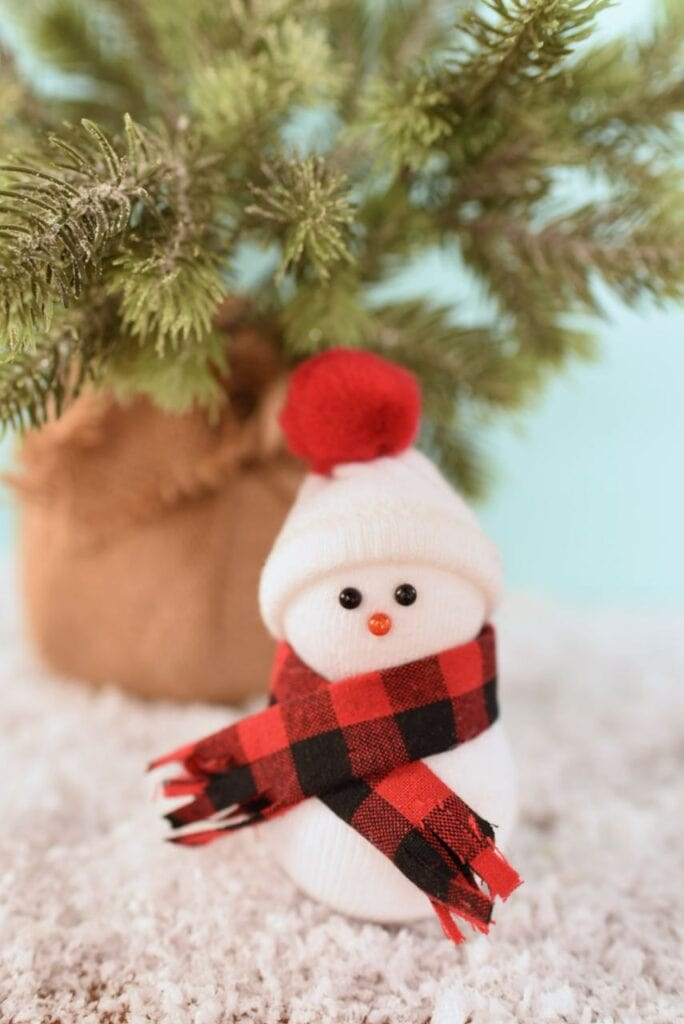 snowman ornament with scarf and hat in front of christmas tree