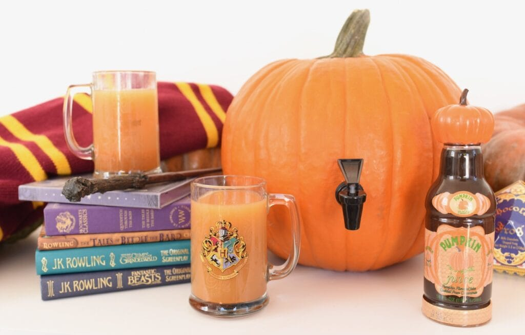 pumpkin juice in mug and bottle next to pumpkin and Harry Potter books