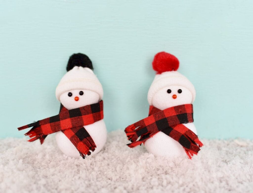 two snowmen ornaments with scarves and hats sitting in snow