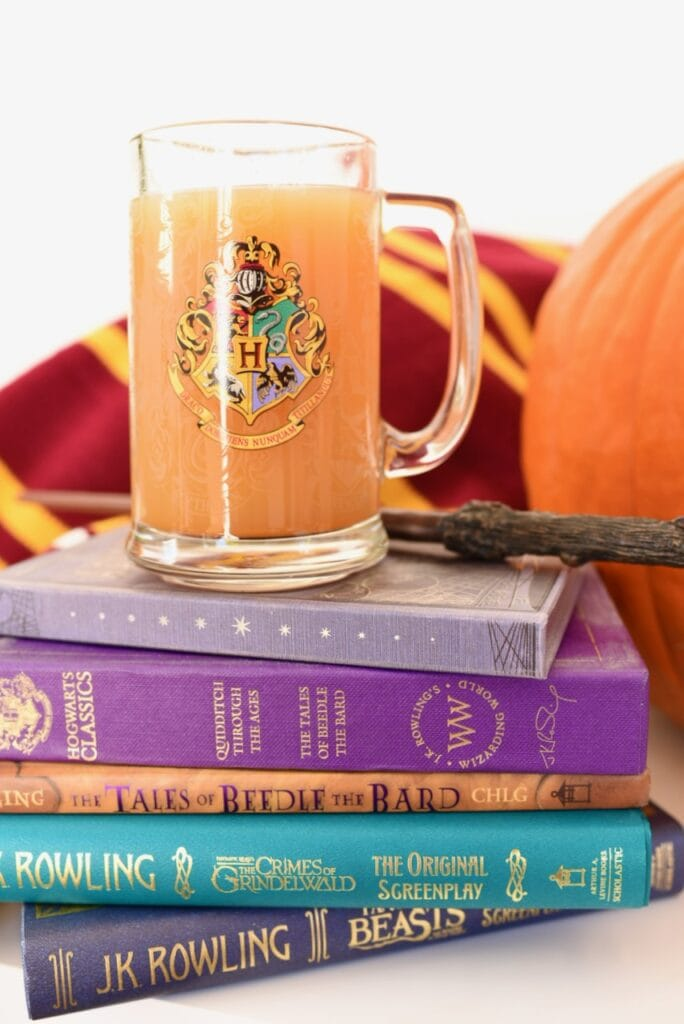 pumpkin juice in clear cup with wand on books