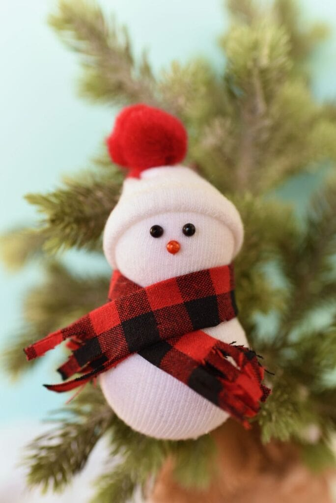 snowman ornament with hat and scarf in christmas tree