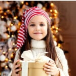girl holding wrapped present in front of Christmas tree