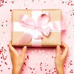 hands holding wrapped gift with bow on pink table with confetti