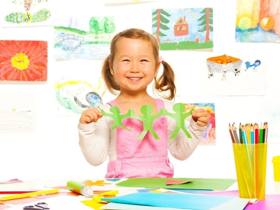 girl holding craft with art on wall