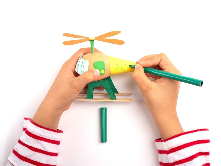 child hands with marker drawing on toy helicopter