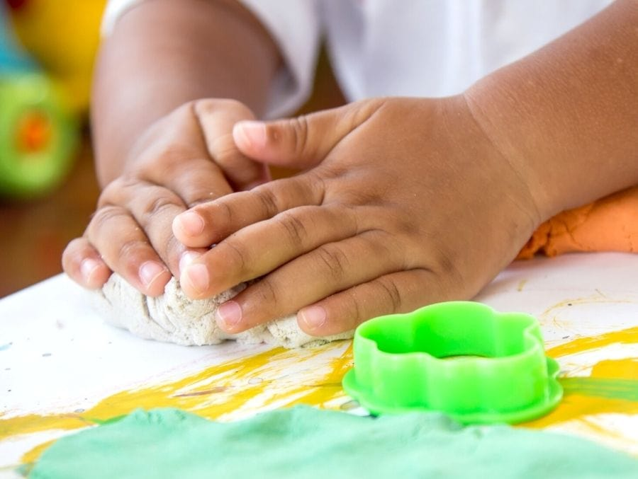 child hands playing with play doh on white table