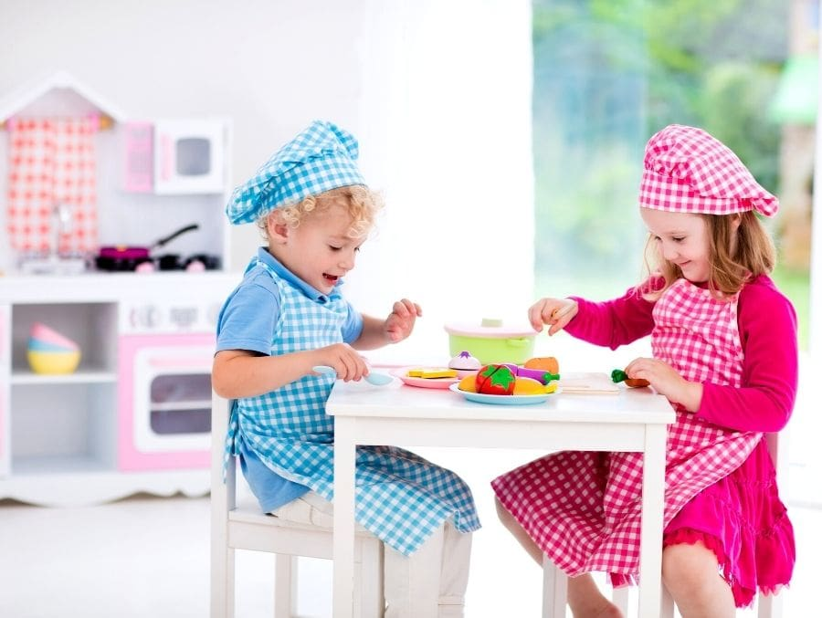 boy and girl with aprons and chef hats at table