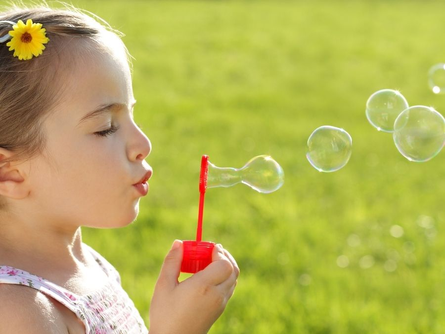 girl blowing bubbles on green grass