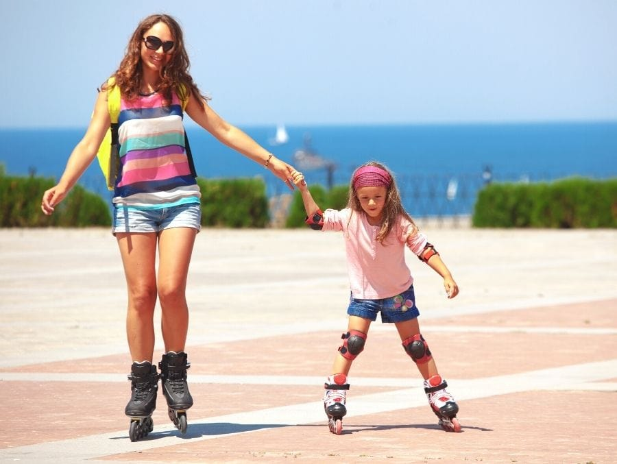mother and daughter roller skating near beach
