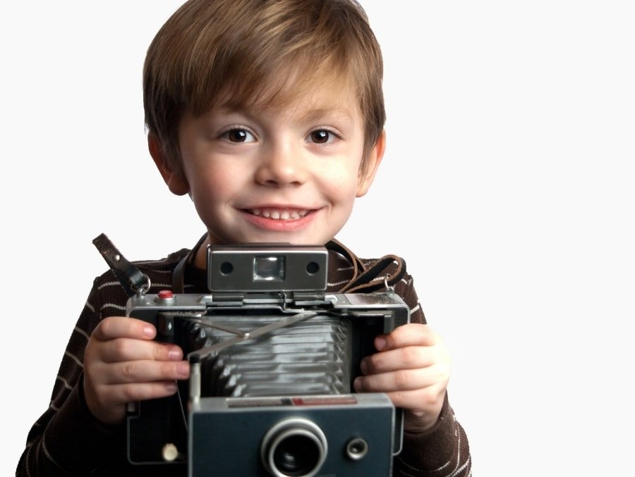 child holding camera in hands