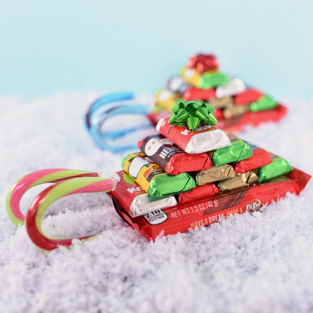 candy sled with chocolate bars and candy canes in snow