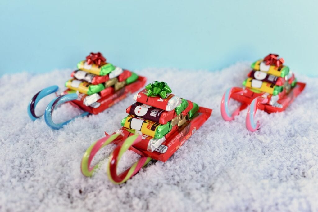 three candy cane sleighs in snow
