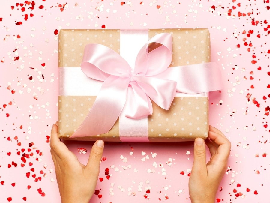 hands holding wrapped gift with pink bow