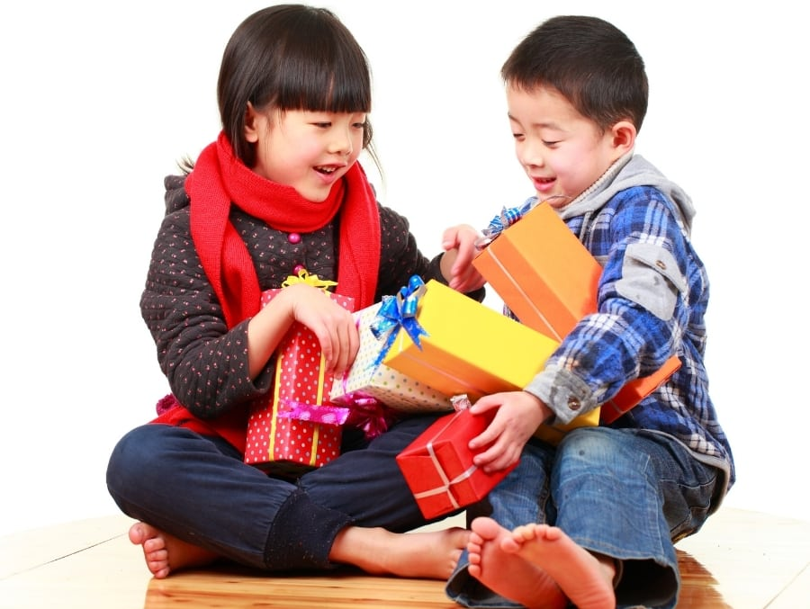 boy and girl holding wrapped non toy gifts for kids