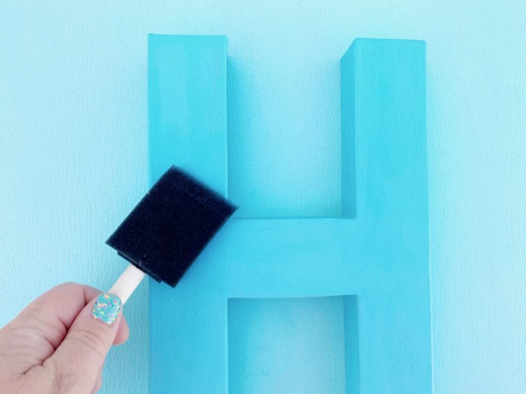 paintbrush painting blue letter H
