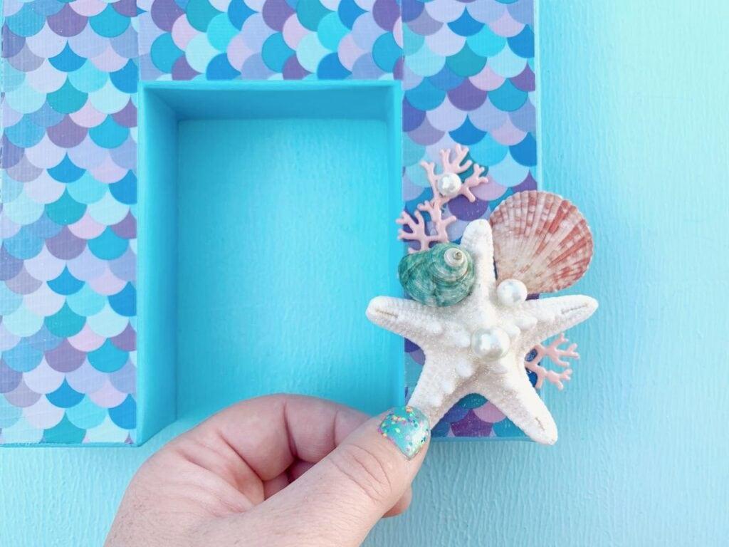 hand touching starfish and seashells on mermaid letter