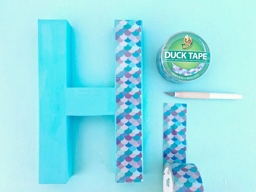 mermaid duck tape on blue letter with craft knife