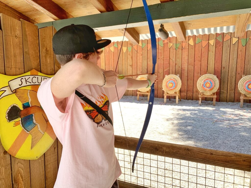 boy shooting arrow with bow at target