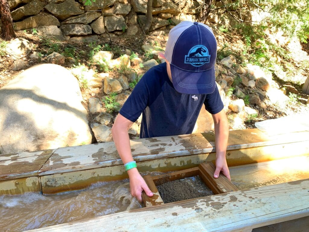boy holding mining tray in water