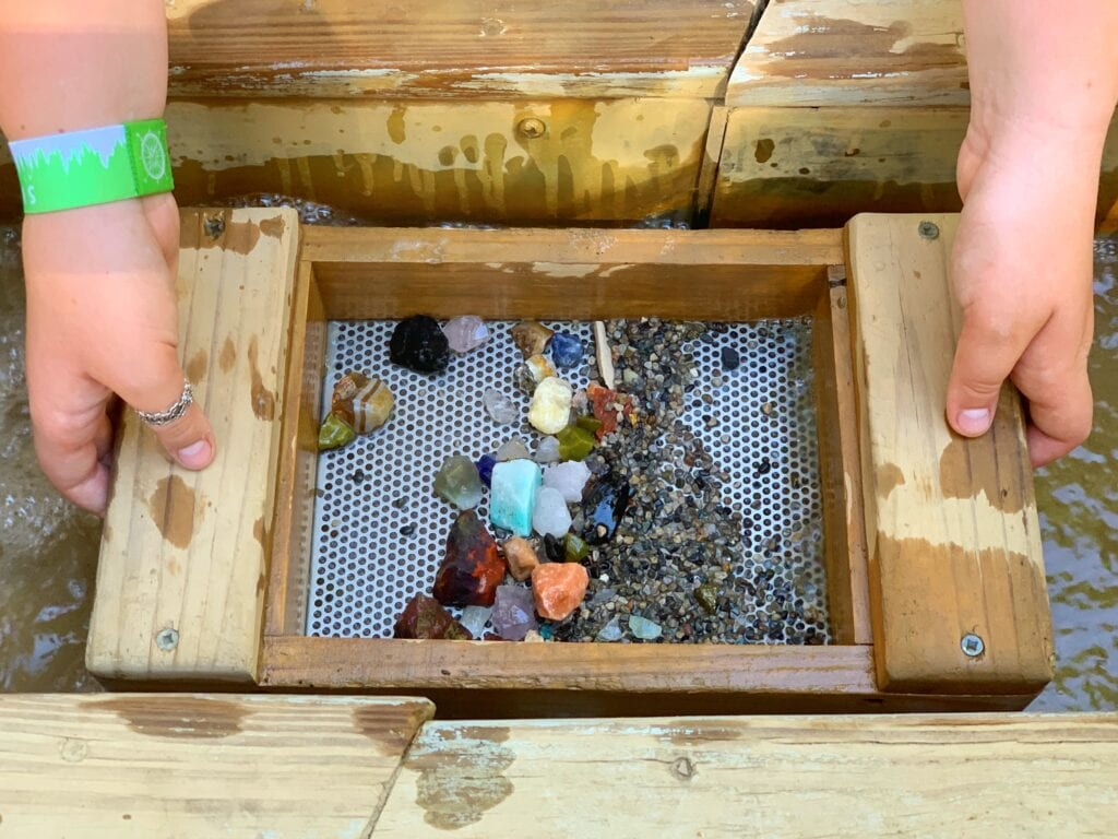 hands holding tray with sand and gemstones