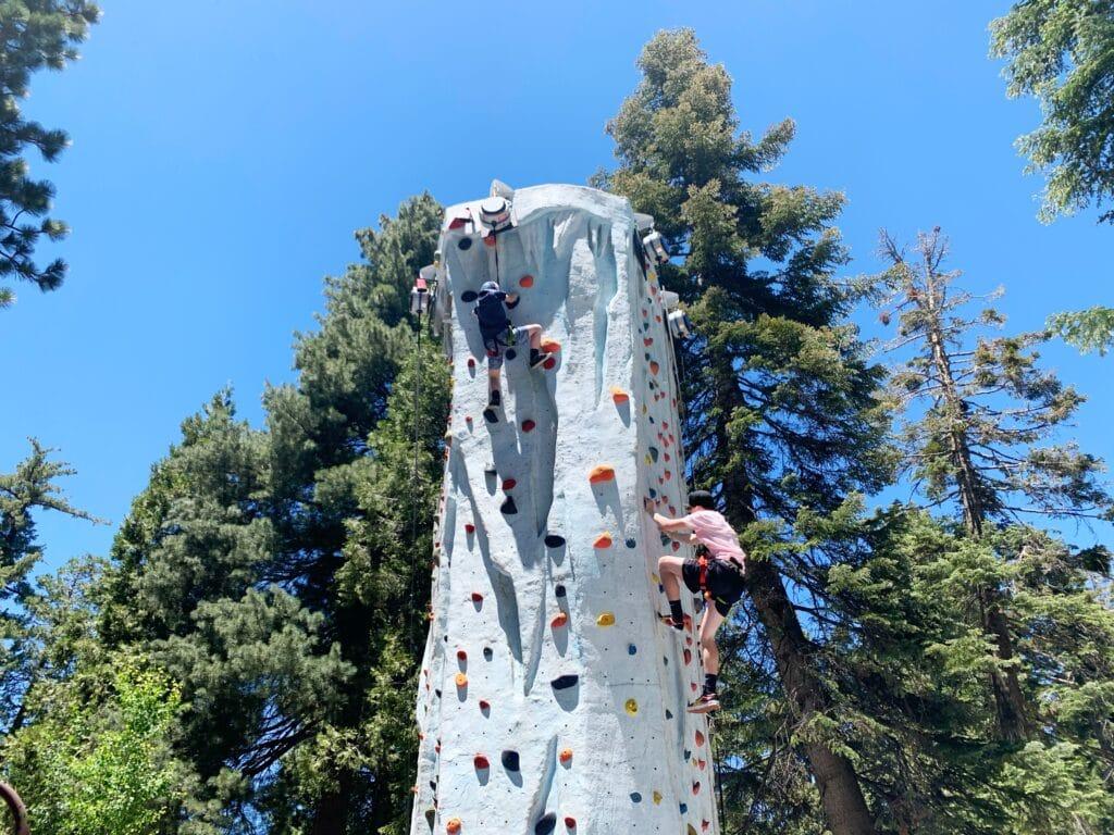boys rock climbing tall tower