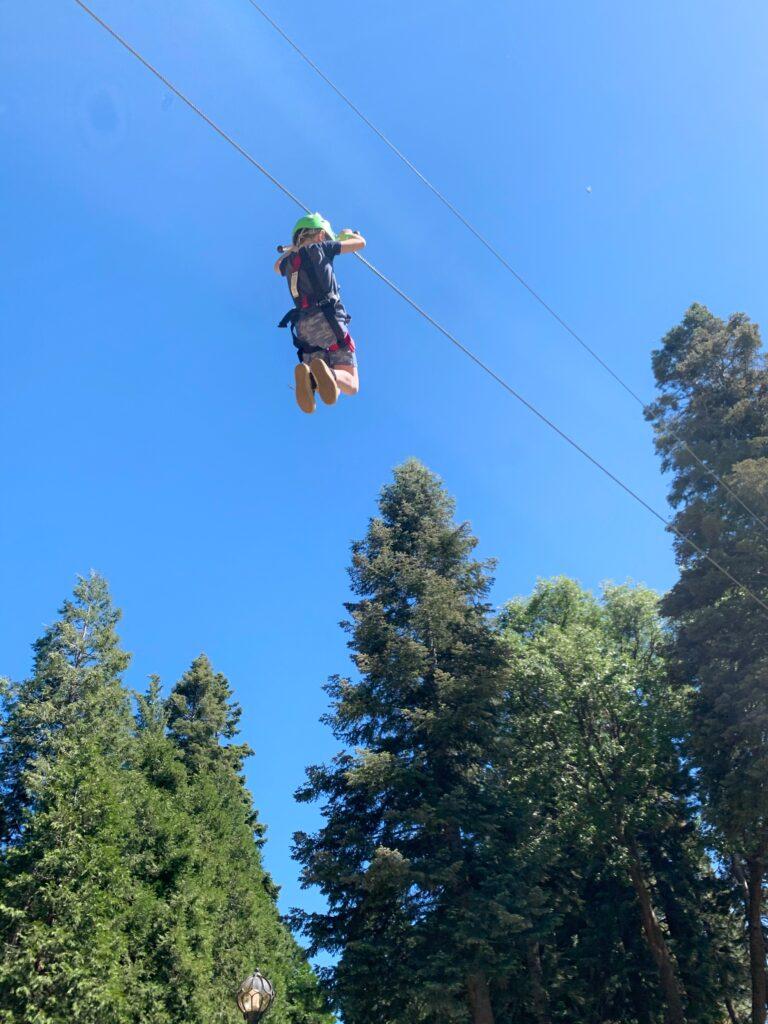 boy zip lining through trees at Skypark at Santa's Village