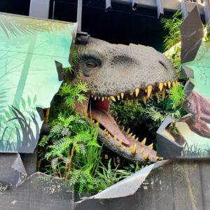 t rex dinosaur breaking through sign