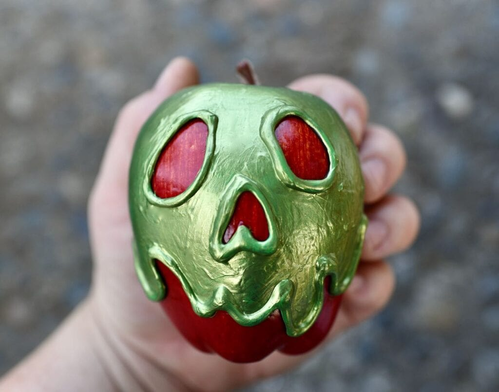 hand holding green poison apple