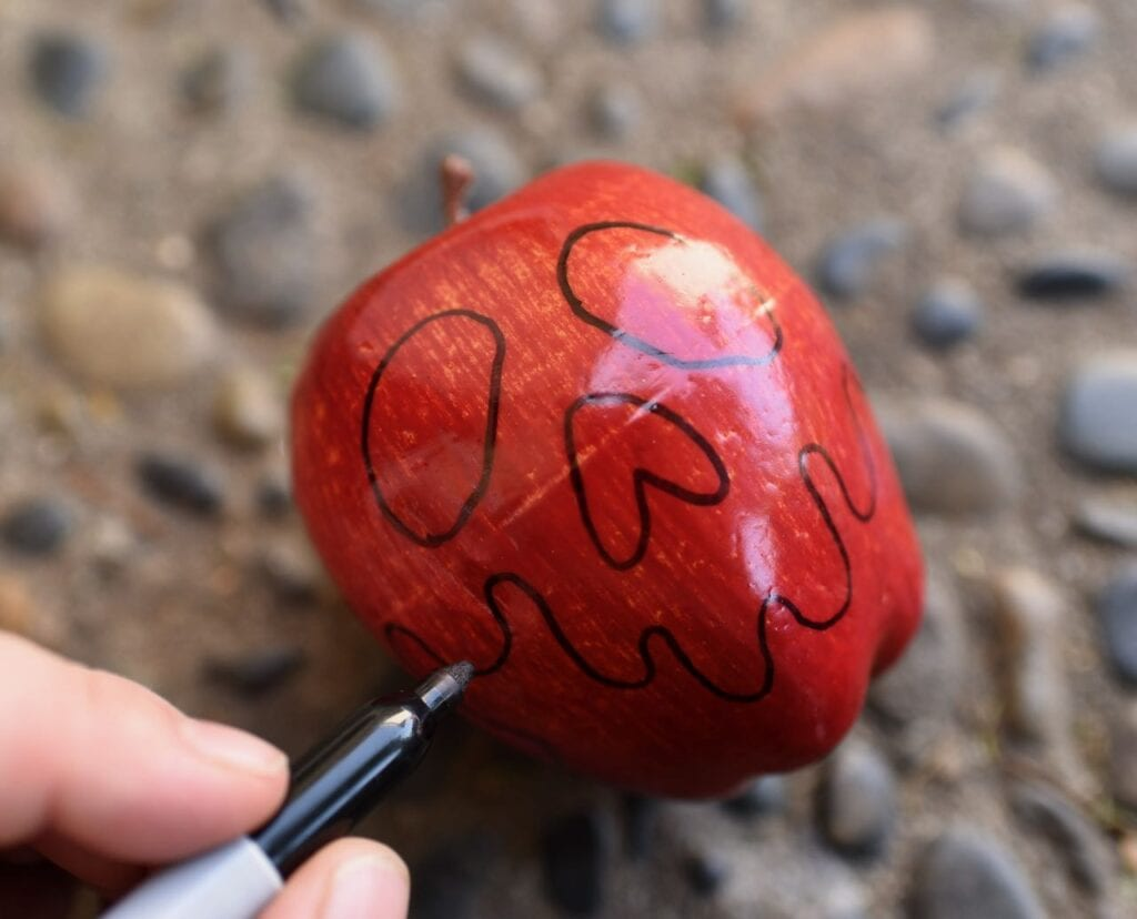 red apple with face draw on